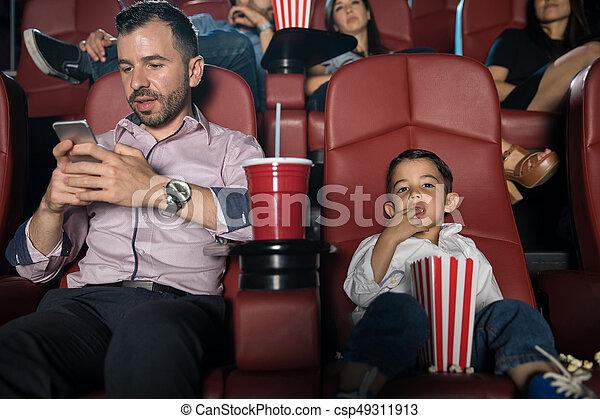 dad checking his phone at the movies busy dad looking at his phone