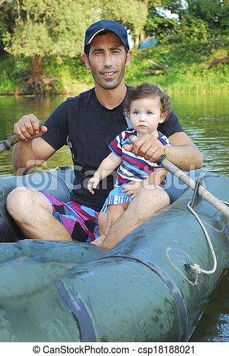 Dad with little daughter sitting in a boat on the river. - csp18188021