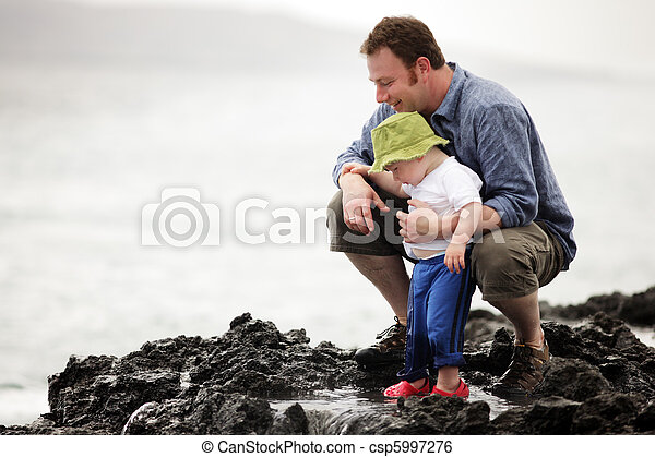 Dad with little son walking outdoors at ocean - csp5997276