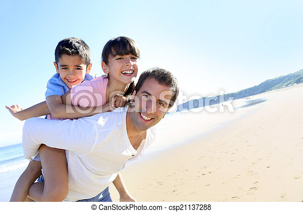Daddy carrying children on his back at the beach - csp21137288