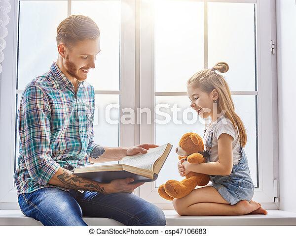 daddy reading a book - csp47106683