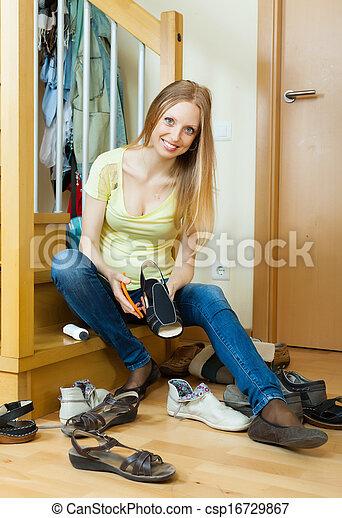 Hausfrau putzt schuhe zu hause. Glückliche blonde hausfrau