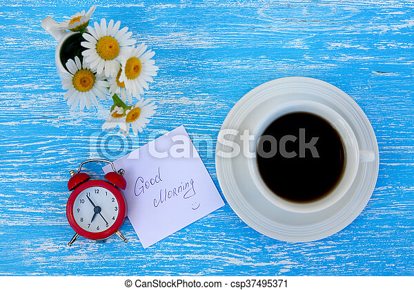 Daisy flowers, alarm clock and cup of coffee with good morning note on rustic blue wooden background - csp37495371