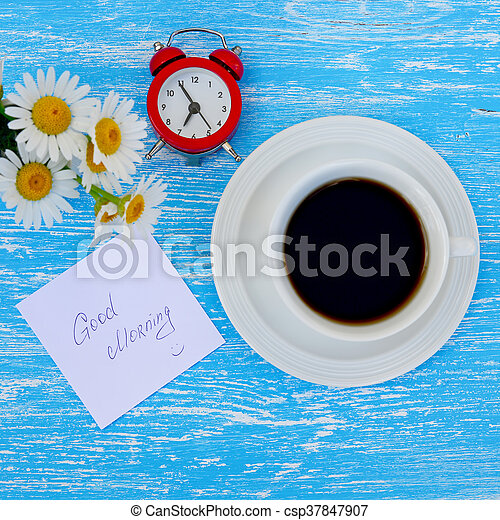 Daisy flowers, alarm clock and cup of coffee with good morning note on rustic blue wooden background - csp37847907