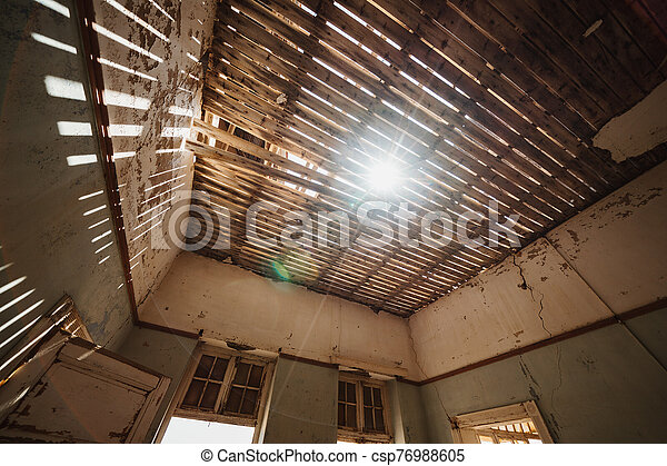 Damaged Building Roof with sunlight shinigh through - csp76988605