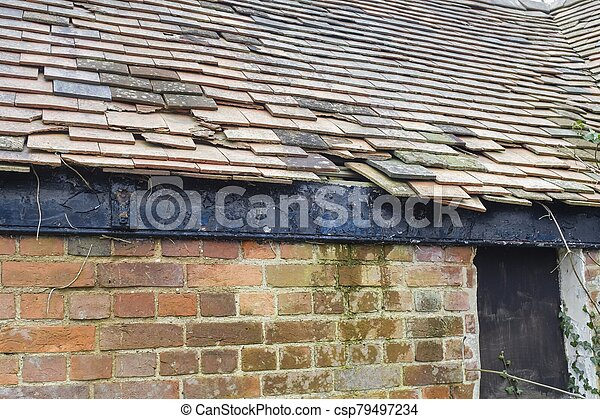Damaged clay roof tiles on a pitched roof, UK - csp79497234