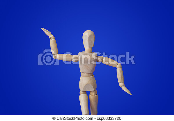 Dancing wooden toy figure on blue - csp68333720