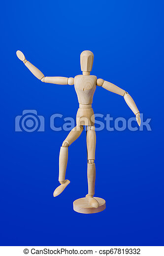 Dancing wooden toy figure on blue - csp67819332
