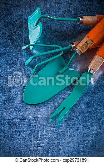 Dandelion trowel hand shovel rake hoe on scratched metallic back - csp29731891