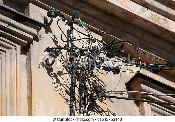 Dangerous installation of electricity cables and wires on the wall of an old building - csp43753140
