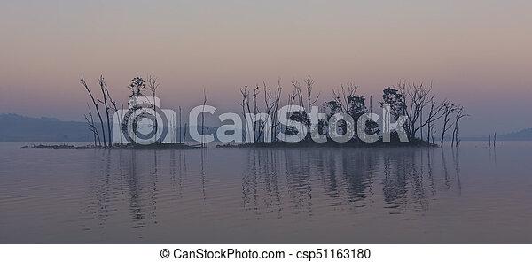 Dark and gloomy landscape of an island on a lake - csp51163180
