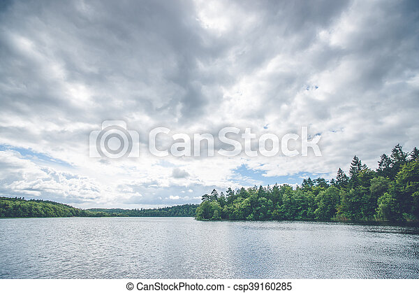 Dark clouds over a forest lake - csp39160285