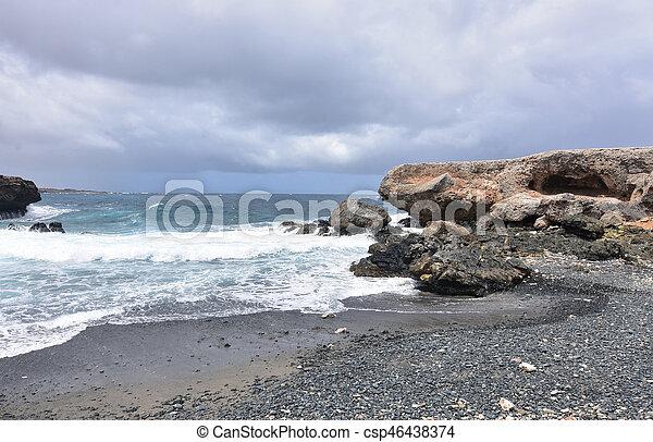 Dark Clouds Over the Black Sand Stone Beach in Aruba - csp46438374
