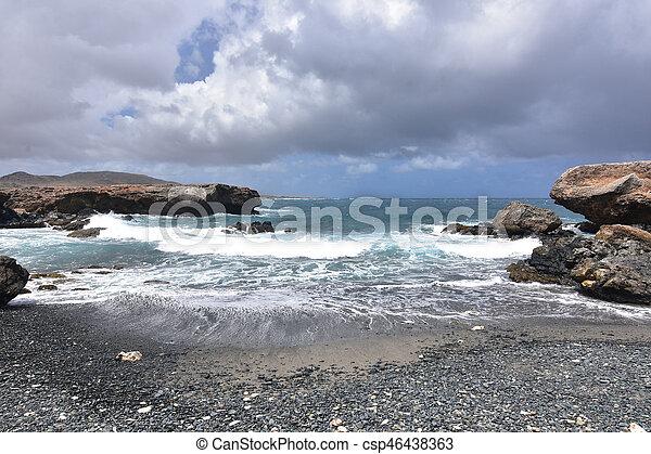 Dark Gray Skies Above the Black Sand Stone Beach in Aruba - csp46438363