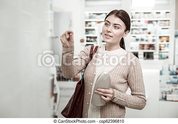 Dark-haired green-eyed woman choosing care cosmetics in pharmacy store - csp62396810