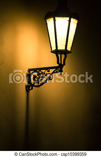 Dark moody picture of old lamp on the wall - csp10399359