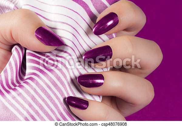 Female Hand With Dark Pink Nails Is Holding Textile On Background