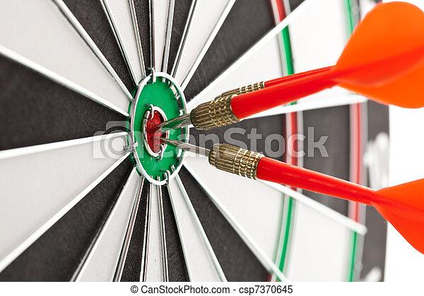 darts hitting the bullseye shallow depth of field shot of darts in