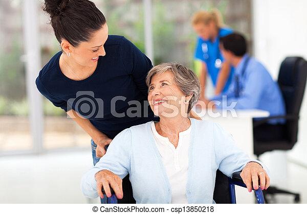 daughter accompanying senior mother to visit doctor - csp13850218