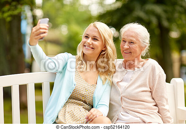 daughter and senior mother taking selfie at park - csp52164120