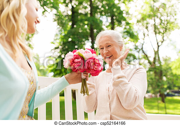 daughter giving flowers to senior mother at park - csp52164166