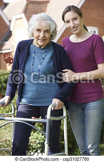 Daughter Helping Senior Mother To Use Walking Frame - csp31027780
