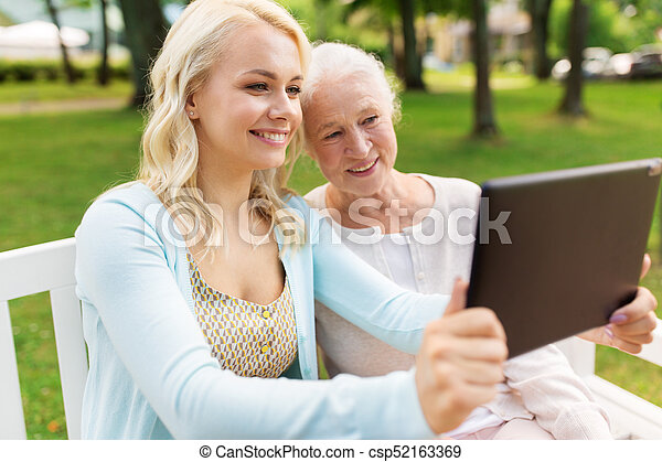 daughter with tablet pc and senior mother at park - csp52163369