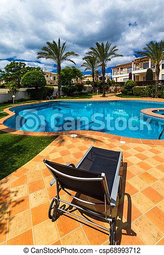 Gran patio trasero con piscina, jacuzzi y sillas de salón. Piscina en el patio trasero. Una piscina increíble y un jardín con palmeras y flores en un día soleado. - csp68993712