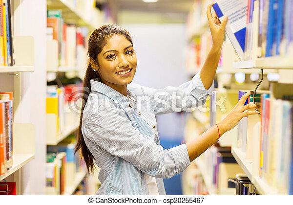 Estudiante universitaria india sacando un libro de la estantería - csp20255467
