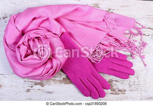 Guantes de lana y chal para la mujer con el bolso de cuero en el fondo de madera vieja rústica, accesorios de mujer, ropa de otoño o invierno
