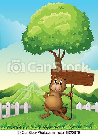 Un castor bajo el árbol con una tabla de madera vacía - csp16320879