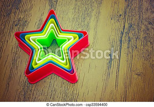 Estrellas de plástico arcoíris en bac de madera - csp33594400