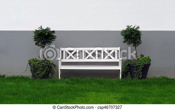 Un banco de madera blanco en el jardín - csp46707327
