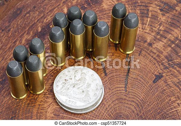 Los cartuchos del revólver 45 y el dólar de plata del salvaje oeste en el fondo de madera - csp51357724