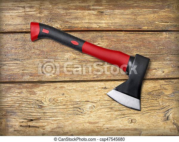 Un hacha roja en una madera - csp47545680