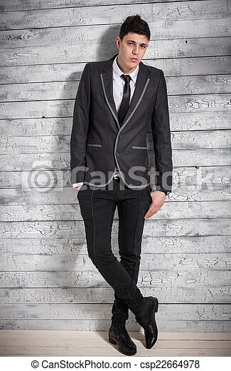 Un hombre elegante con traje apoyado contra una pared de madera blanca - csp22664978