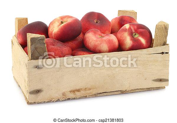 Néctarinas planas en una caja de madera - csp21381803