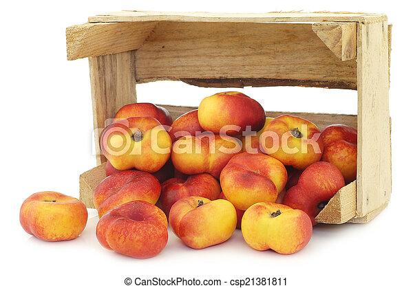Néctarinas planas en una caja de madera - csp21381811