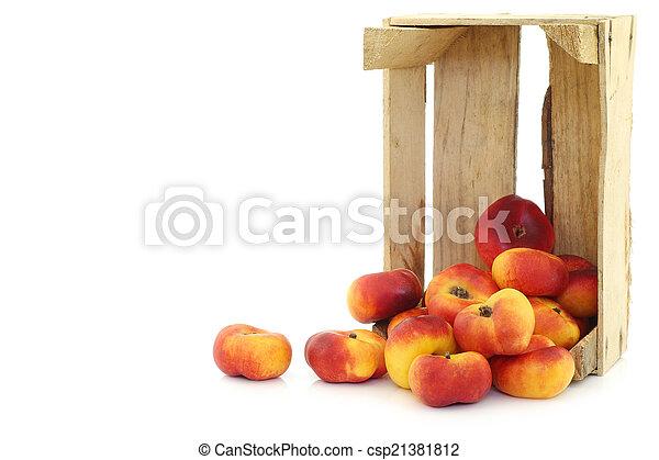 Néctarinas planas en una caja de madera - csp21381812