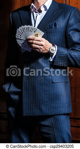 El hombre de traje posa con tarjetas de fondo de madera - csp29403205