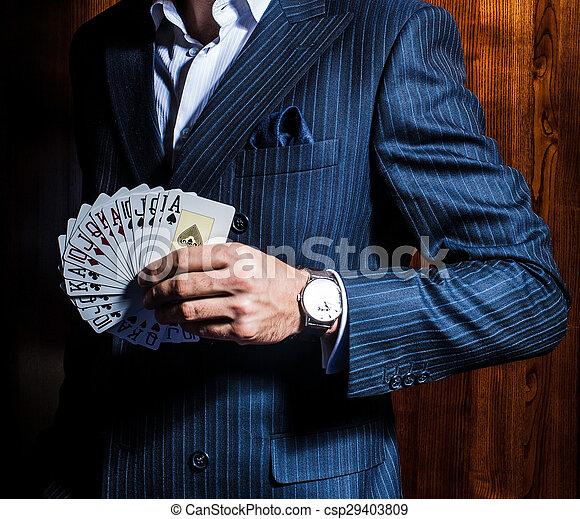 El hombre de traje posa con tarjetas de fondo de madera - csp29403809