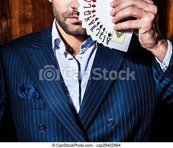 El hombre de traje posa con tarjetas de fondo de madera - csp29402994