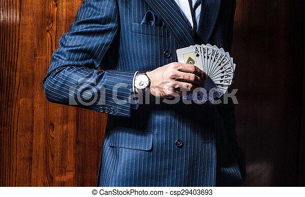 El hombre de traje posa con tarjetas de fondo de madera - csp29403693