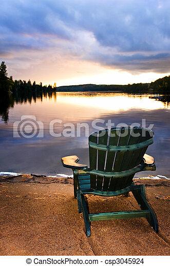 Una silla de madera al atardecer en la playa - csp3045924