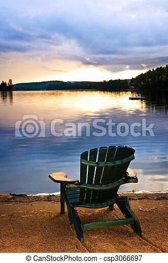 Una silla de madera al atardecer en la playa - csp3066697