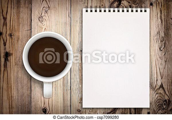 Un cuaderno con una taza de café en un fondo de madera - csp7099280