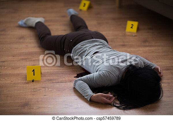 dead woman body in blood on floor at crime scene