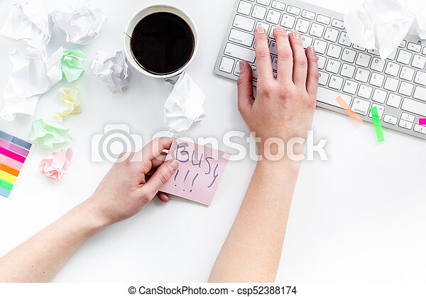 Deadline in office. Hand takes sticker Busy. desk covered with crumpled paper and stationery on white background top view - csp52388174