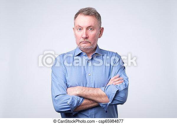 Un hombre serio con los brazos cruzados y una expresión de la sartén posando en la pared gris - csp65984877