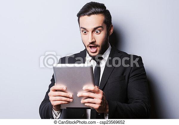 debout, examiner, sien, tenue, tablette, tablet., marque, jeune, formalwear, gris, quoique, contre, fond, numérique, nouveau, surpris, homme - csp23569652